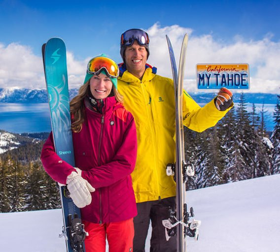 Smiling couple holding Tahoe license plate
